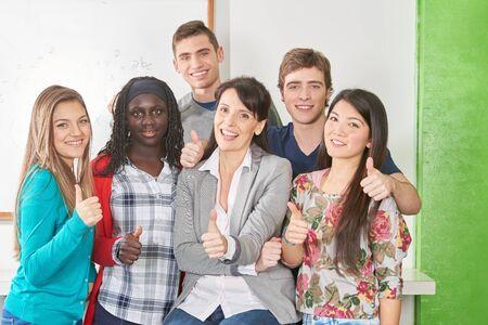Los estudiantes en la escuela levantan el pulgar con el maestro.