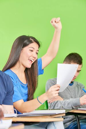 Asian girl cheers happily at school after successful class work