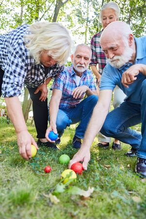 Seniors playing boules as a competition in the garden in the retirement home or on vacation Reklamní fotografie