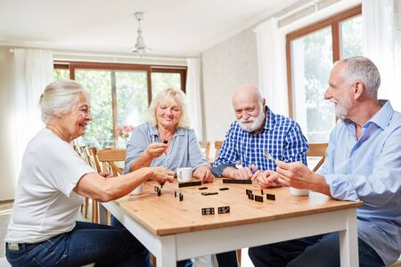 Seniors as friends play dominoes together in a retirement home or retirement home Stock Photo