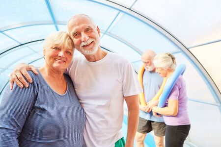 Happy senior couple makes aqua fitness in the swimming pool at the rehab clinic