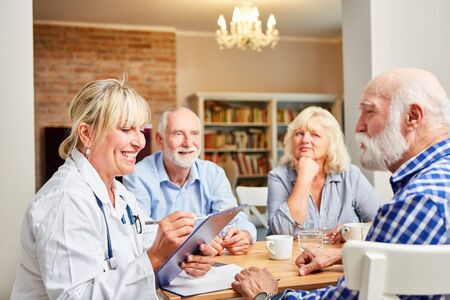 Female doctor with clipboard together with seniors in a group therapy session