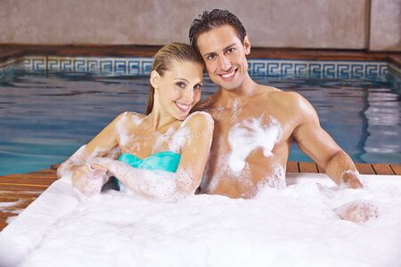 Happy couple sitting together in the jacuzzi in the spa Фото со стока