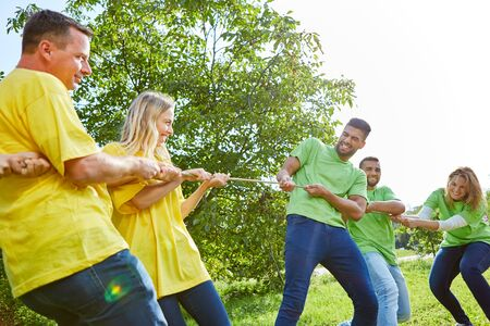 Two sports teams tug-of-war in a teambuilding workshop on a meadow