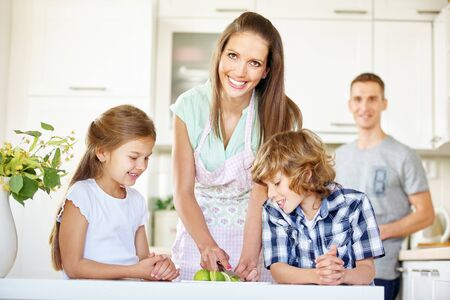 Happy family with two children cuts fruit in the kitchen