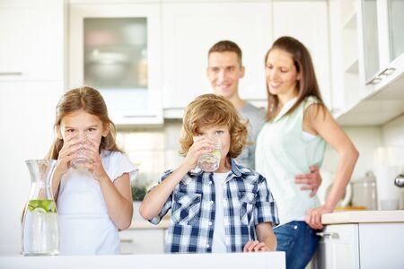 Kinderen drinken vers water met limoenen in de keuken in het bijzijn van hun ouders