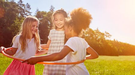 Multicultural girls play together with a hoop in the summer in a meadow