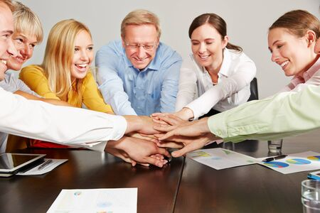 Many happy business people stack hands in the office for motivation Stock fotó