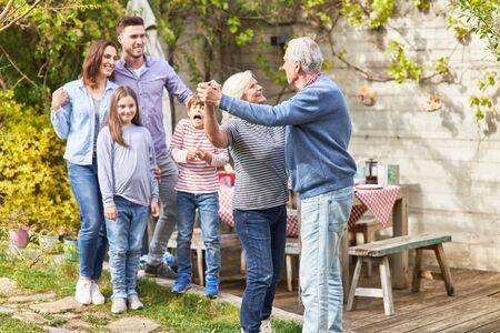 Glückliches Seniorenpaar tanzt zusammen im Garten und feiert den Hochzeitstag Standard-Bild