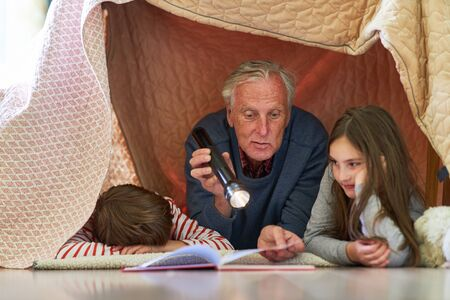 Grandfather with flashlight reads grandson to children from a book at night