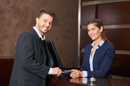 Un uomo d'affari paga in un hotel con la sua carta di credito credit