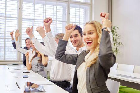 Animando a la gente de negocios en la oficina aprieta los puños y levanta los pulgares