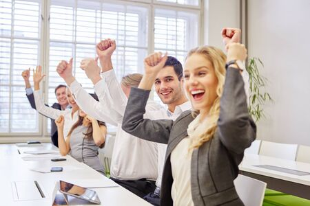 Cheering business people in the office clench fists and hold thumbs up
