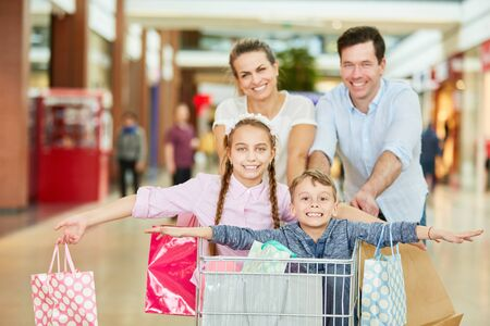 Cheerful parents and silly kids in shopping cart in shopping mall