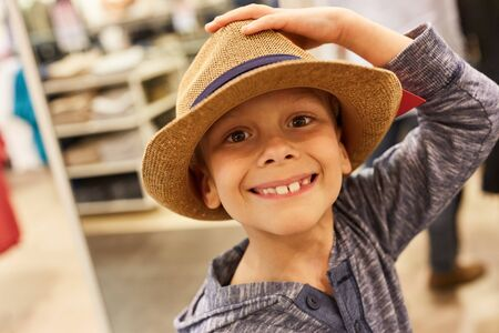 Happy boy in hat buying in a fashion store in the shopping center Stock Photo