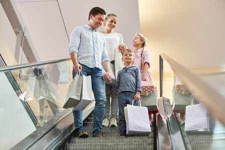Parents and two children on an escalator with shopping bags in the shopping center Reklamní fotografie