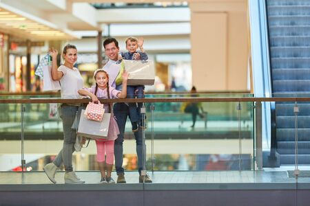Parents and two kids waving shopping bags at shopping mall