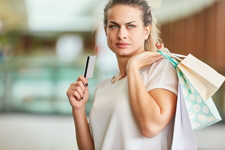 Woman as a customer and consumer with credit card is thinking while shopping