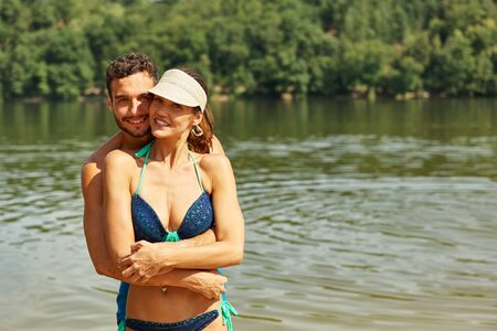 Happy couple goes on summer vacation by the lake