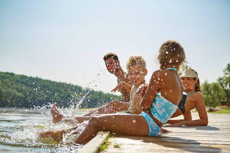 Familia feliz junto al lago en verano sosteniendo los pies en el agua
