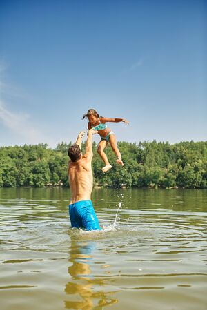 Father throws his daughter into the water in the lake in summer