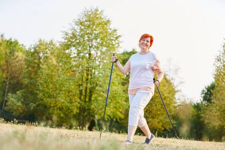 Happy woman doing Nordic walking in the summer in the park