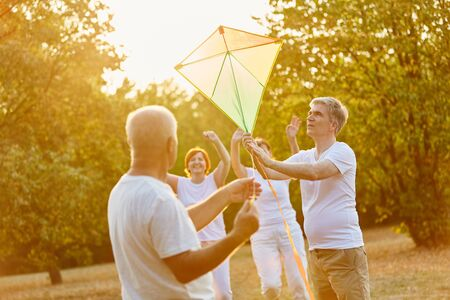 Seniors fly a kite together in autumn