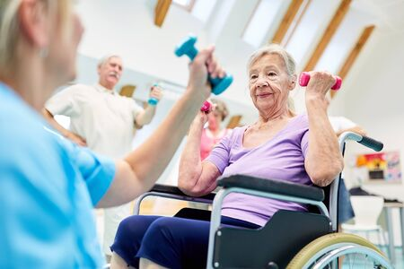 Senior woman in wheelchair doing rehab workout with dumbbells after stroke Stock Photo
