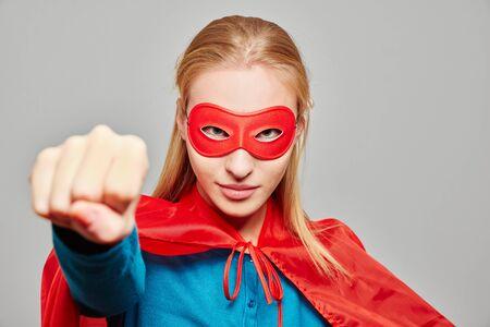 Junge blonde Frau verkleidet als Superheld an Karneval