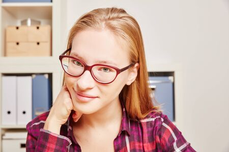 Smiling blonde student with glasses looks at the camera Stock Photo