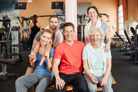 Happy group with elderly woman sitting in fitness center