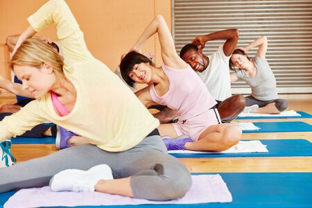 People practice yoga together in class at a fitness center 스톡 콘텐츠