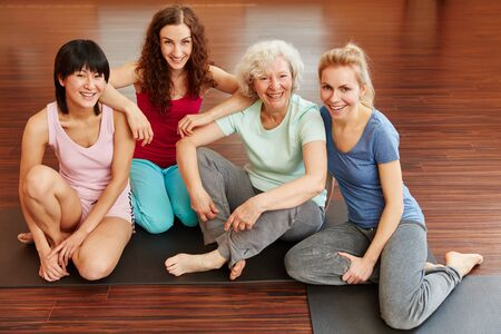 Happy women sitting together in yoga class at the gym 스톡 콘텐츠