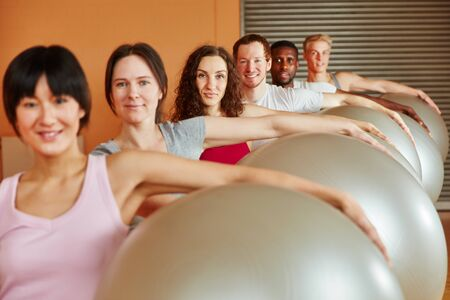 Group in fitness class doing exercise with exercise ball
