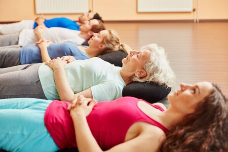 Group does meditation for relaxation after the yoga class