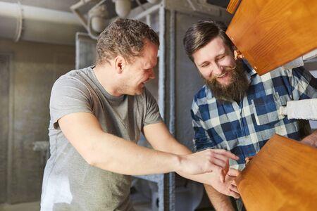 Carpenter apprentice and instructor check a wooden board in the carpentry Фото со стока