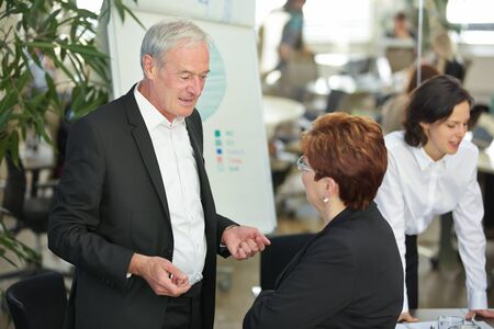 Two older business people talk to each other in the office