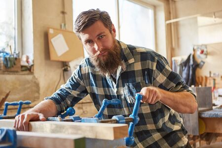 Hipster carpenter as a furniture maker works with a wooden workpiece on a vice