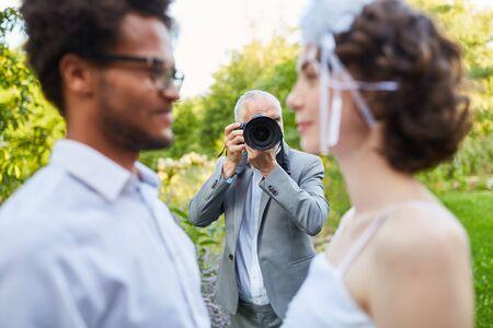 Wedding photographer photographs newlyweds on wedding day in nature Banco de Imagens