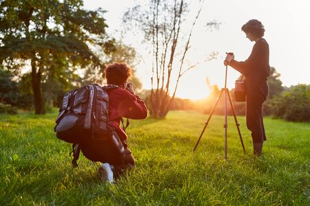 Photographers team as landscape photographers at sunrise in nature 스톡 콘텐츠