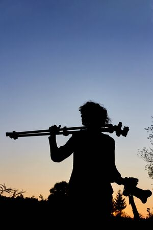 Photographer as silhouette with camera and tripod in the blue hour