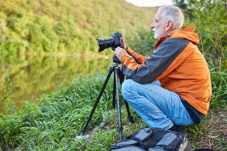 Senior photographer as a professional nature photographer with camera and tripod 스톡 콘텐츠