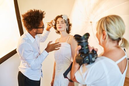 Make-up artist styling the bride for the photo shoot on the wedding day