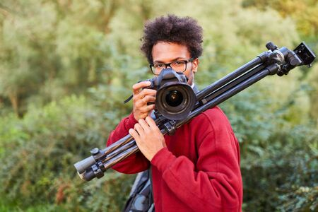 Young photographer as a landscape photographer in nature with camera and tripod 스톡 콘텐츠