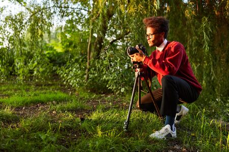 Nature photographer in landscape photography as a hobby with camera and tripod