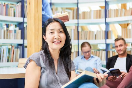 Asian woman as a student reading a book in the reading room in the university library