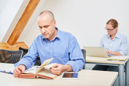 Man in a seminar for adult education reads concentrated in a book