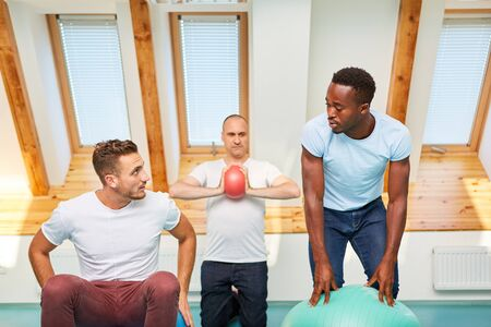 Group of young men is exercising with gym ball in a Pilates class in the gym