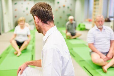 Trainer or physiotherapist does back exercises with seniors as rehabilitation sport Stock Photo