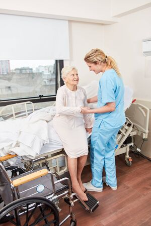 Nursing lady cares for disabled senior citizen and helps her get up